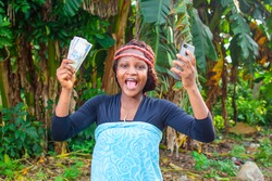 A happy female african farmer with local beads on her head, farming hoe on her shoulder, joyfully raising a farming hoe and smart phone up in a farm