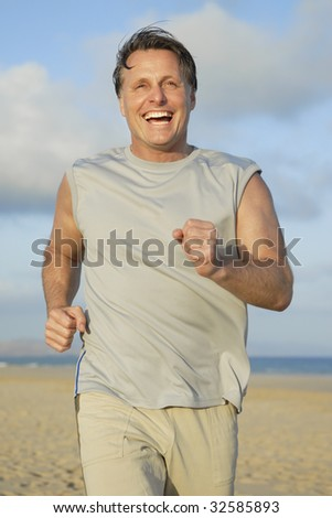 A happy forties man jogging on beach.