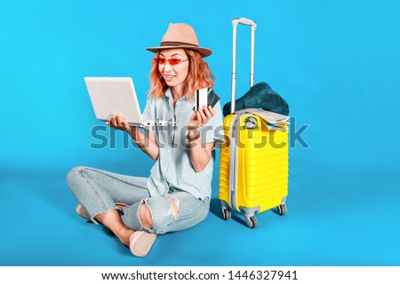 A happy girl buys a tourist trip or a tour using a laptop and a Bank credit card. Voyage e-commerce concept. Shooting in the Studio on a colored background. #1446327941