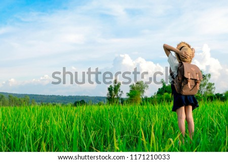 A happy girl enjoying nature in meadow. Outstretched arms, breathing fresh air with a cloudy blue sky in the background - concept of clean atmosphere.