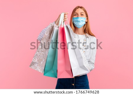 A happy girl in a medical mask on her face, posing with shopping bags and looking at the camera on a pink background. Shopping, coronavirus, quarantine