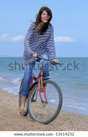 A Happy girl in a striped vest cycling on the sea background