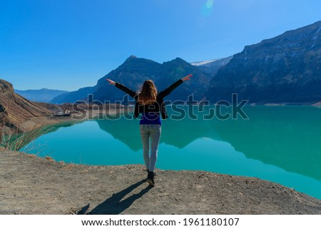 A happy girl stands alone on the shore of the Irganay reservoir in Dagestan with emerald water and reflections of the mountains. The concept of deliberate and long-term travel and self-immersion.