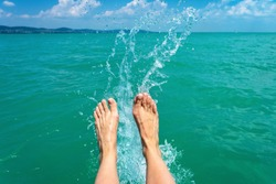 A happy girl woman is kicking feet on a sea lake and splashing water on a sail boat summertime holiday