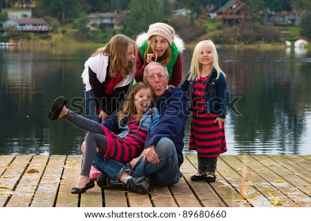 A happy Grandfather with a group of kids on a dock at a lake outside.