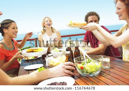 A happy group of teenage friends sitting at a table at the seaside drinking beer and eating their lunch