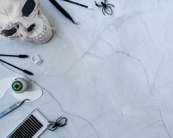 A happy Halloween themed beauty background. Treatment tools and products arranged on left side of frame with spooky accessories include spiders cobwebs & skeleton heads. Flat lay style with copy space