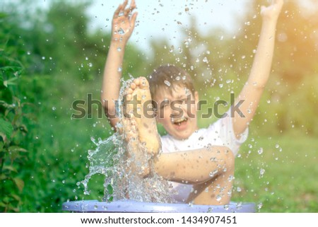 A happy happy happy boy frolicking in the basin. outdoors in summer, spraying water. #1434907451