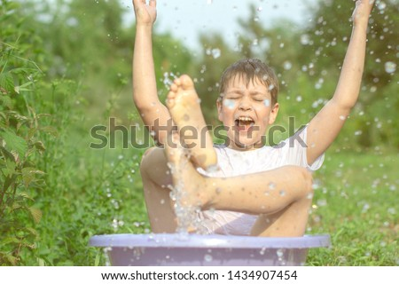 A happy happy happy boy frolicking in the basin. outdoors in summer, spraying water. #1434907454