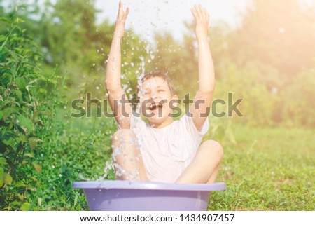 A happy happy happy boy frolicking in the basin. outdoors in summer, spraying water. #1434907457