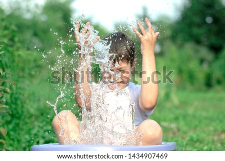 A happy happy happy boy frolicking in the basin. outdoors in summer, spraying water. #1434907469