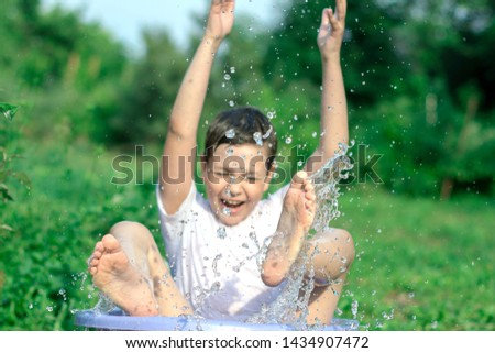 A happy happy happy boy frolicking in the basin. outdoors in summer, spraying water. #1434907472