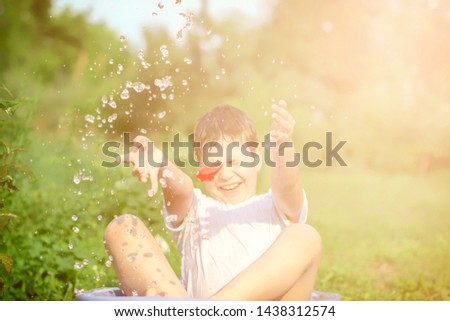 A happy happy happy boy frolicking in the basin. outdoors in summer, spraying water.