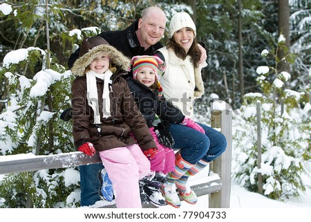 A happy, healthy family outside in the snow. - stock photo