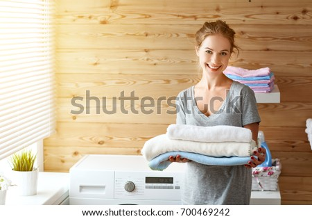a Happy housewife woman in laundry room with washing machine  \r