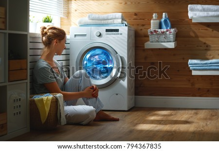 a Happy housewife woman in laundry room with washing machine   #794367835
