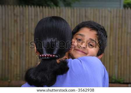 A happy Indian kid hugging his mother
