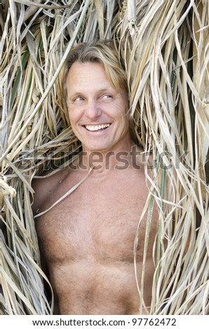 A happy laughing forties man having fun amongst dried grass during a day at the beach.