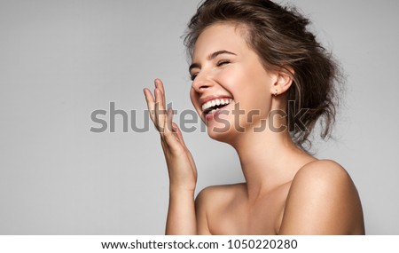A happy laughing young woman with perfect skin, natural make-up and a beautiful smile. Female portrait with bare shoulders on a gray background #1050220280