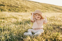 A happy little child laughs poses and plays with a hat while sitting on the grass in a summer park at sunset