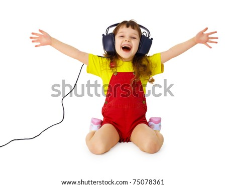 A happy little girl listens to music with headphones isolated on white background
