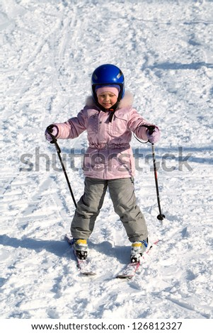 A happy little girl off skiing with slides
