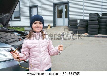 A happy little girl with a wrench on a background of car service.  Repair service