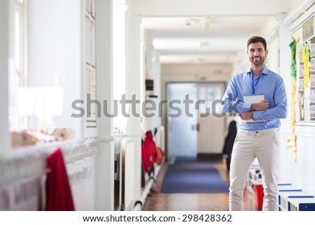 A happy male teacher dressed smartly and smiling in a school corridor.