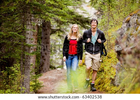 A happy man and woman hiking on a camping trip