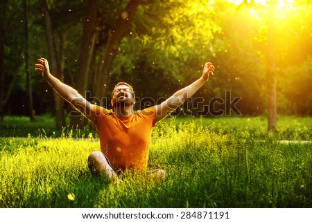 A happy man is relaxing on green grass with squint eyes and raised up to sky arms at sunny summer day at park background. Concept of wellbeing and healthy lifestyle #284871191