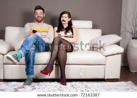 A happy man is watching TV in silence because he taped his girlfriend's mouth