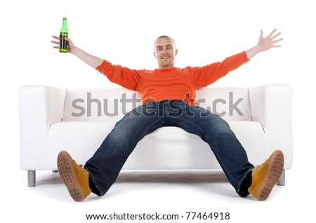 A happy man sitting on a white sofa with arms and legs outspread, holding a green bottle of beer.