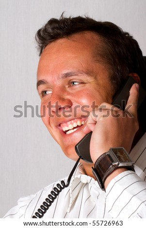 A happy man talking on a telephone