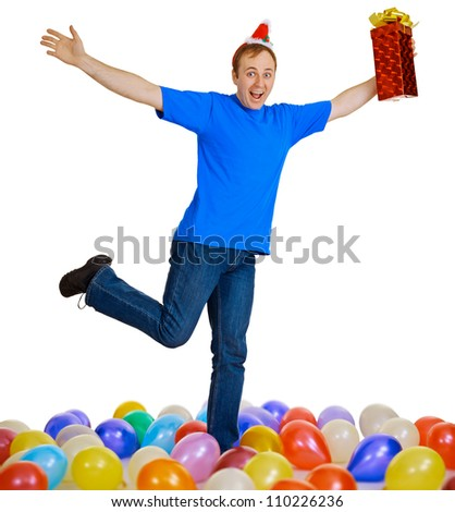 A happy man with a Christmas gift dancing among balls