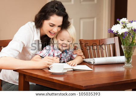 A happy mother and son sitting at table writing and drawing