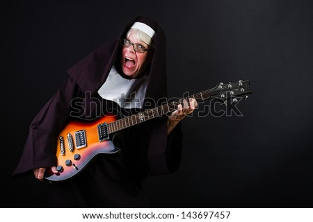 A happy nun playing the guitar with a smile on her face.