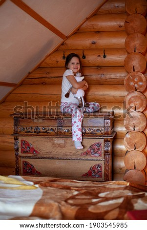 a happy, overjoyed girl sits on an old wooden dresser with one leg hanging down and hugs a toy cow in the bedroom of a rustic log house. Stock photo ©