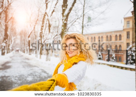 A happy playful blond curly hair woman dancing and playing with yellow knitted hat in the snow in the winter city park. Sun glare effect.