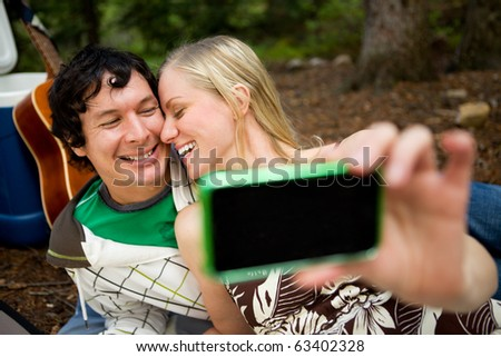 A happy playful couple on a picnic taking a self portrait
