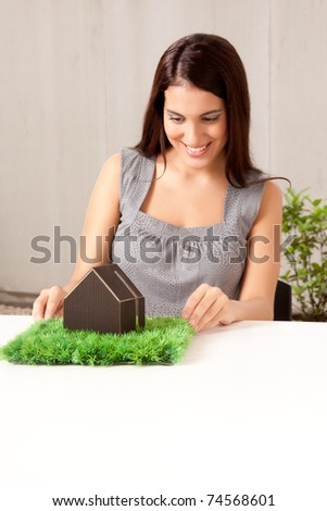A happy professional woman looking at a model house with grass