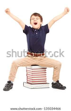 A happy schoolboy raised his hands gesturing happiness, seated on a pile of books against white background
