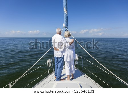 A happy senior couple embracing at the front or bow of a sail boat on a calm blue sea looking to an clear horizon