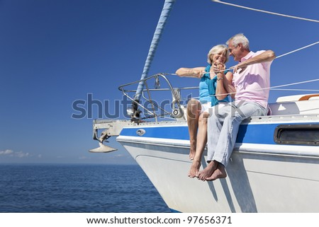 A happy senior couple holding hands, laughing while sitting on a sail boat on a calm blue sea