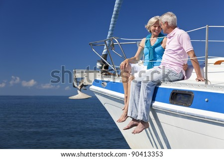 A happy senior couple sitting on the deck of a sail boat on a calm blue sea