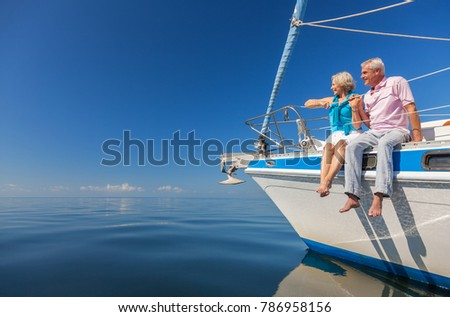 A happy senior couple sitting on the side of a sail boat on a calm blue sea #786958156