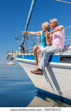 A happy senior couple sitting on the side of a sail boat on a calm blue sea, the woman is pointing to the horizon #786958153