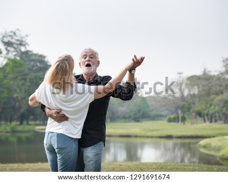 A happy senior couple smiling dancing in a park on a sunny day. relax in the forest spring summer time. free time, lifestyle retirement grandparents concept