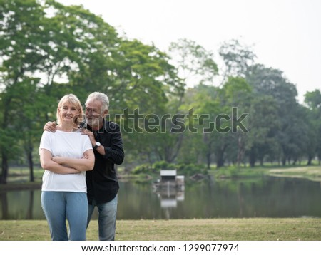 A happy senior couple stand in a park on a sunny day. Relax in the forest spring summer time. free time, lifestyle retirement grandparents concept