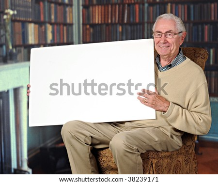 A happy senior man holding a blank sign in a home library.