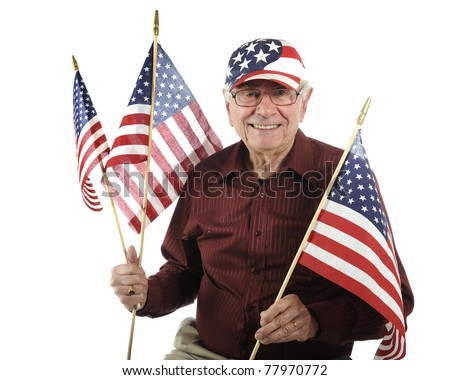 A happy senior man wearing a stars-and-stripes hat while holding three American flags.  Isolated on white.